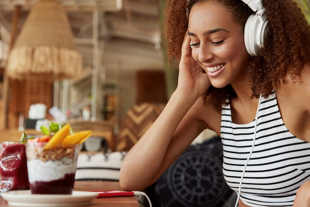 ヘッドフォンで幸せな若いアフリカ系アメリカ人女性は、プレイリストにアップロードするためにインターネットのウェブサイトで音楽を検索し、居心地の良いカフェテリアでwifiに接続された現代の携帯電話を使用しています。流行に敏感な女の子がオーディオを聴く