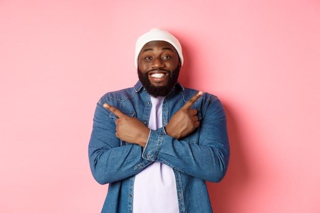 Felice giovane hipster afroamericano che punta le dita lateralmente, sorride e mostra due scelte, mostra offerte, in piedi su sfondo rosa