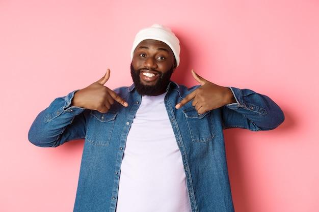 Felice giovane hipster afroamericano che indica se stesso t-shirt, sorridendo soddisfatto, in piedi su sfondo rosa.