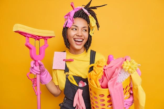 幸せな若いアフリカ系アメリカ人の主婦はモップを保持し、洗濯物の洗面器は喜んで見えます