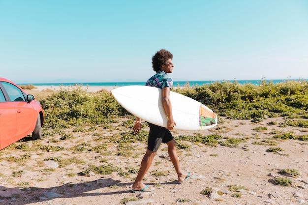Счастливый молодой афроамериканец мужчина идет с доски для серфинга вдоль берега моря
