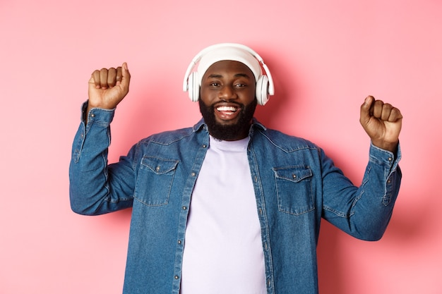 Happy young african-american man dancing and listening music in headphones, pump fists up and smiling, standing over pink background