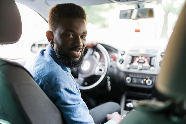 車を運転して幸せな若いアフリカ系アメリカ人の男