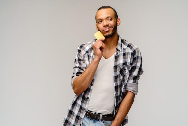 Счастливый молодой афро-американский мужчина держит наличные или дисконтную карту
