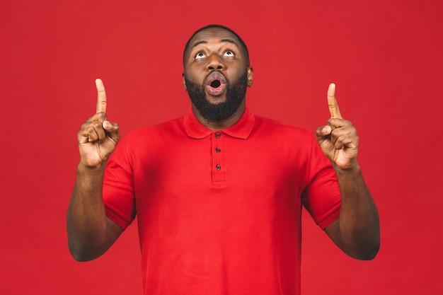興奮した表情で見上げる、カジュアルな笑顔で幸せな若いアフリカ系アメリカ人の男