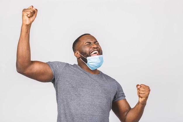 無菌のフェイスマスクで幸せな若いアフリカ系アメリカ人の男。勝者のジェスチャー。
