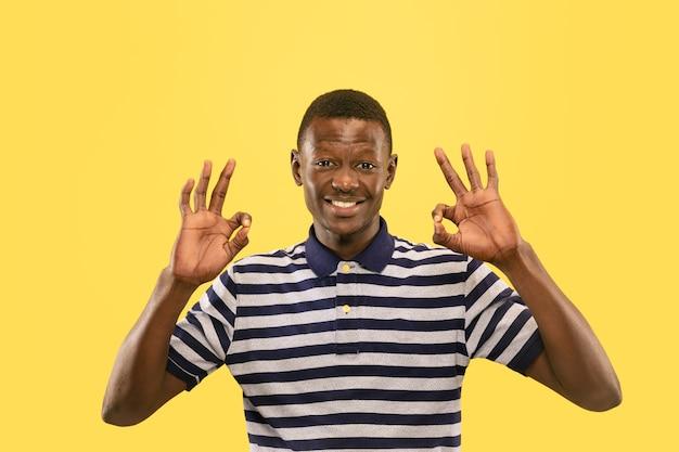 Счастливый молодой афро-американский мужчина, изолированные на желтой студии