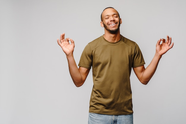 Счастливый молодой афроамериканец медитирует с закрытыми глазами над серой стеной
