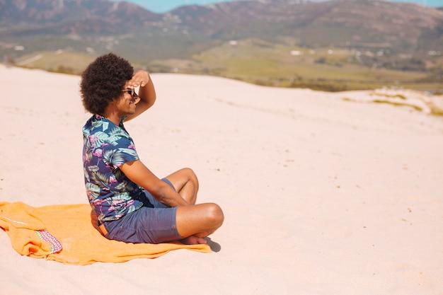 Счастливый молодой афроамериканец человек, сидящий на пляже