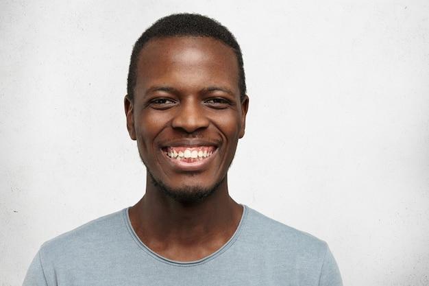 幸せな若いアフリカ系アメリカ人の男が元気に彼の完璧なまっすぐな白い歯を見せて笑って、孤立したポーズ