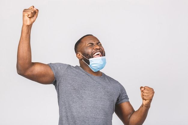 Happy young african american man in sterile face mask. winner gesture.