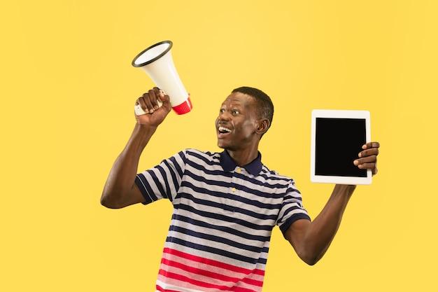 黄色のスタジオの背景、顔の表情に分離されたタブレットを持つ幸せな若いアフリカ系アメリカ人の男。美しい男性の半分の長さの肖像画。人間の感情、顔の表情の概念。