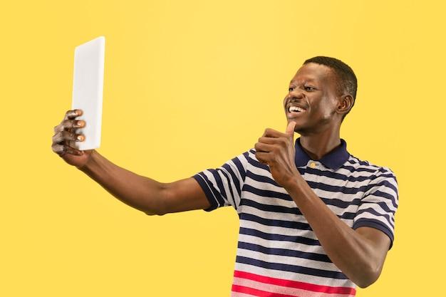 노란색 스튜디오 배경, 표정에 고립 된 태블릿 행복 한 젊은 아프리카 계 미국인 남자. 아름다운 남성 절반 길이 초상화. 인간의 감정, 표정의 개념.