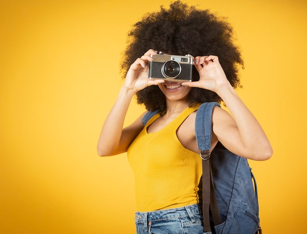 A happy young african american photographer holding retro fil yellow background