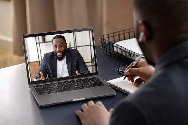 행복한 젊은 아프리카계 미국인이 노트북을 사용하여 동료와 채팅을 하고 있습니다. 영상통화, 자가 격리 개념