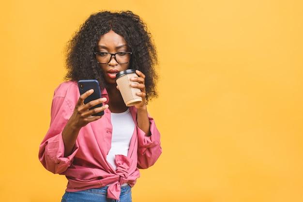 Счастливая молодая афро-американская женщина небрежно одетая стоя, разговаривает по мобильному телефону, держа чашку кофе на вынос.
