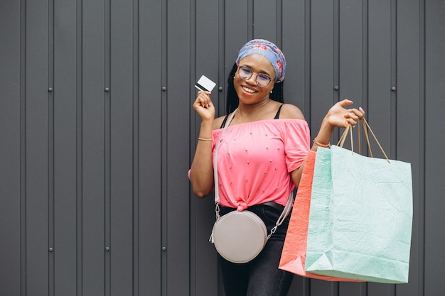Happy young african american woman holding shopping bags and credit card