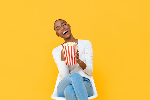 Happy young african american woman laughing while watching movie with popcorn in hand isolated