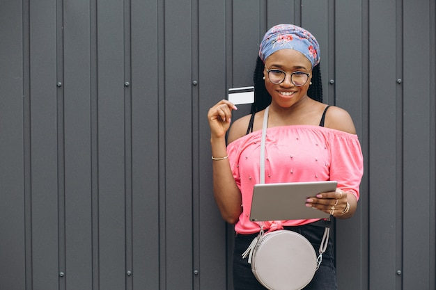 Happy young african american woman make shopping in the tablet with credit card at the gray wall