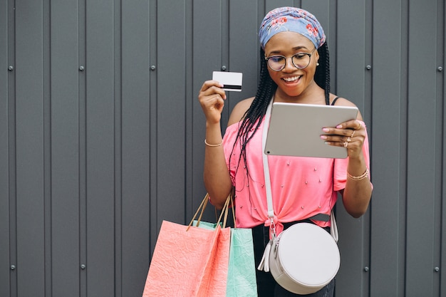 Happy young african american woman make shopping in the tablet with credit card and holding shopping bags at the gray wall