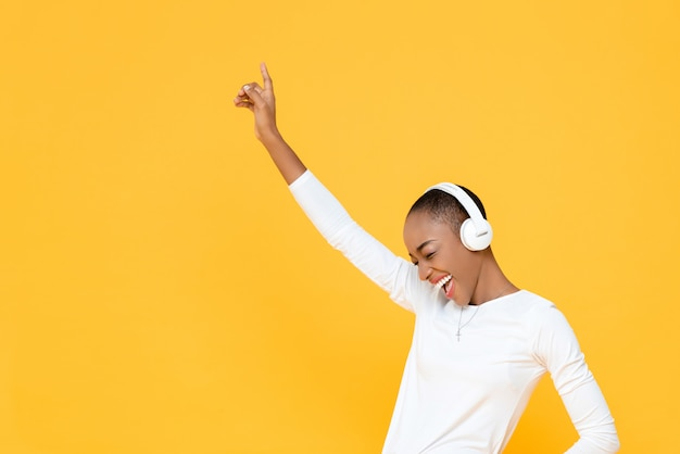Happy young african american woman raising hand up while listening to music in wireless headphones on yellow isolated wall