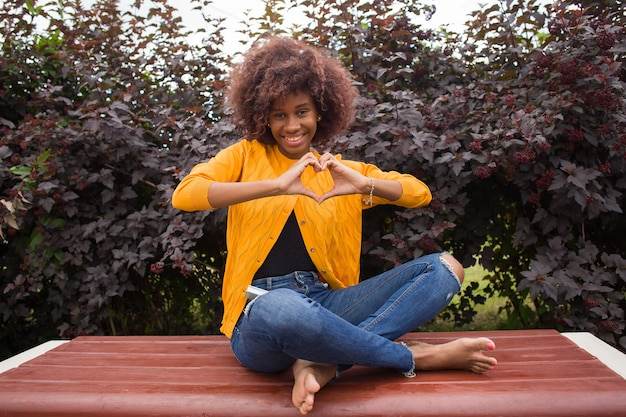 A happy and young african american woman shows a heart with her hands