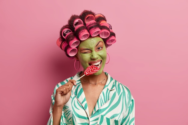 Happy young african american woman winks eye, bites delicious lollipop, applies green mask on face, hair curlers, dressed casually, undergoes beauty treatments