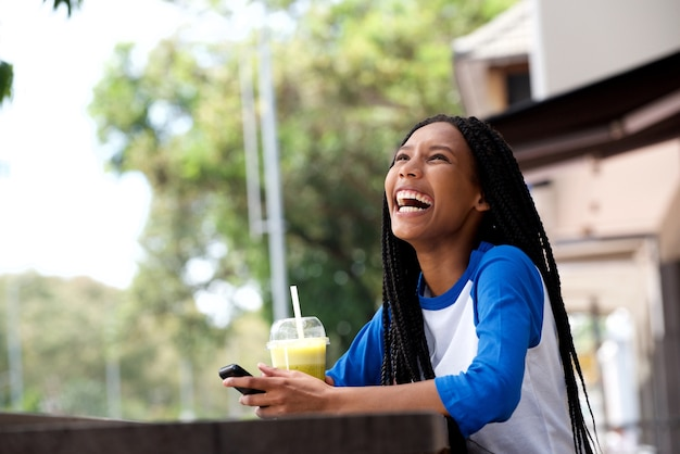 Happy young african american woman with mobile phone at cafe