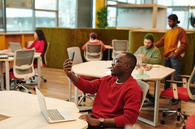 Счастливый молодой африканский бизнесмен в повседневной одежде и очках делает селфи или видеозвонок, сидя на рабочем месте против коллег