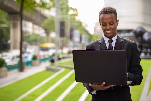 Счастливый молодой африканский бизнесмен, используя портативный компьютер на открытом воздухе