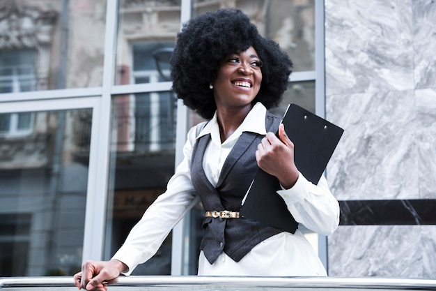 Happy young african businesswoman holding clipboard in hand looking away