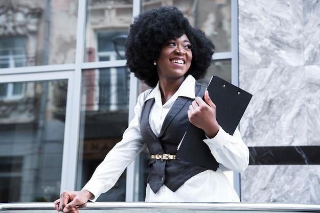 Счастливая молодая африканская коммерсантка держа доску сзажимом для бумаги в руке смотря прочь