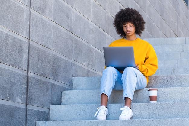 Счастливый молодой африканский студент работника коммерсантки ослабляя сидеть на лестнице города. глядя на экран ноутбука, смотрите онлайн-видео вебинара на компьютере, отдыхающем на рабочем месте, завершив работу