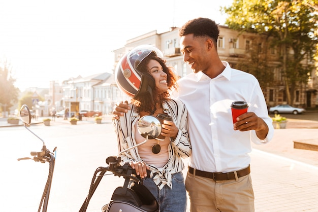 Happy young african couple drinking coffee while standing near the modern motorbike on the street and looking to each other