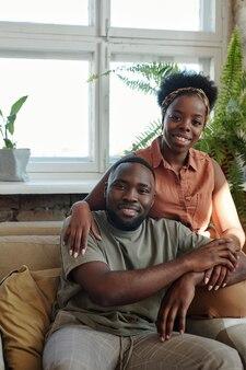 緑の国内植物と窓に対してカメラの前に座って笑顔であなたを見ているカジュアルウェアで幸せな若いアフリカのカップル