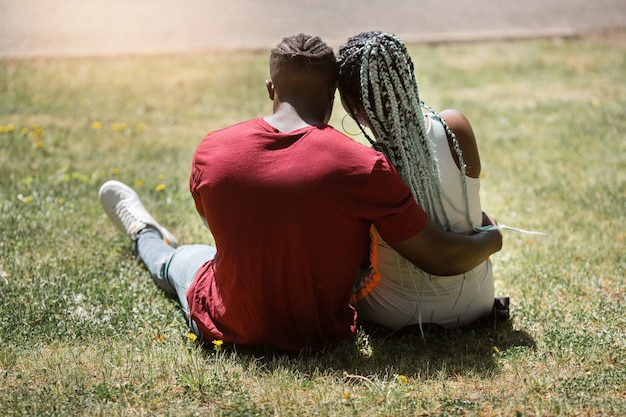 Happy young african couple of people sitting in a summer park on the grass