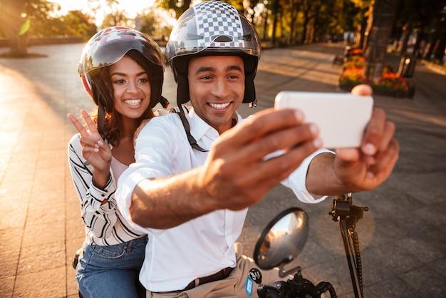 屋外の現代的なバイクの上に座って、スマートフォンでselfieを作る幸せな若いアフリカカップル