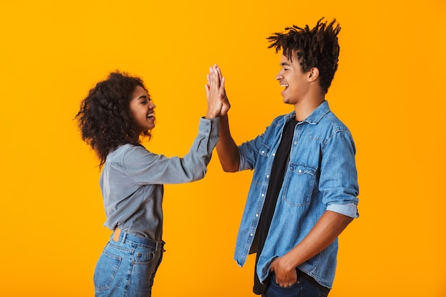 Happy young african couple wearing casual clothes standing isolated, giving high five