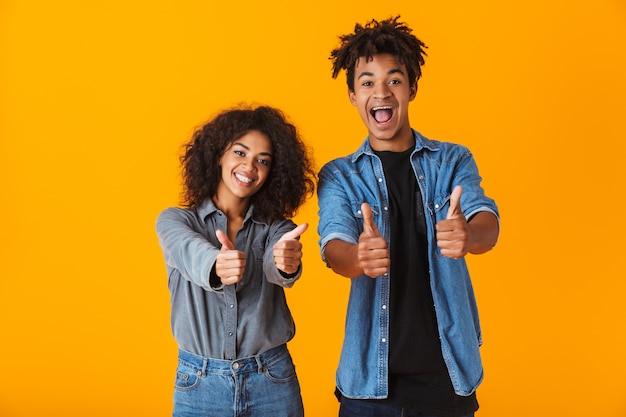Happy young african couple wearing casual clothes standing isolated, giving thumbs up