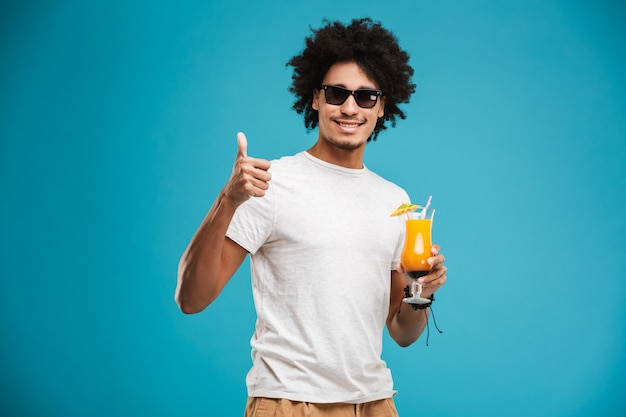Happy young african curly man drinking cocktail showing thumbs up.