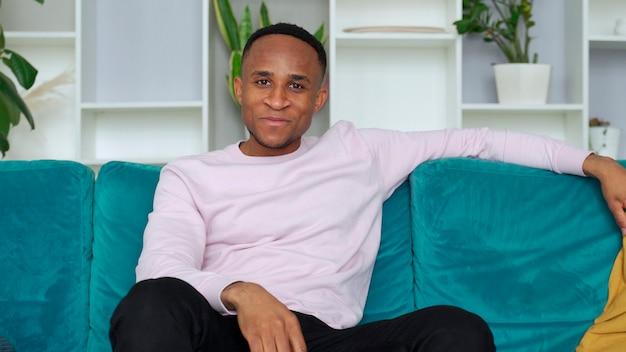 リビングルームでテレビ番組を見ているリモコンを持って自宅の居心地の良いソファでリラックスして幸せな若いアフリカ民族の男