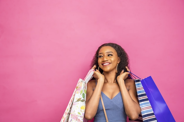 ピンクで隔離の買い物袋でポーズをとって幸せな若いアフリカの女性