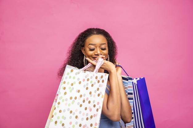 ショッピングバッグでポーズをとって幸せな若いアフリカの女性