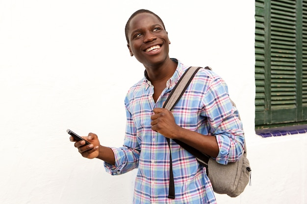 Happy young african guy outside with bag and smart phone