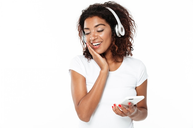 Happy young african lady listening music in headphones.