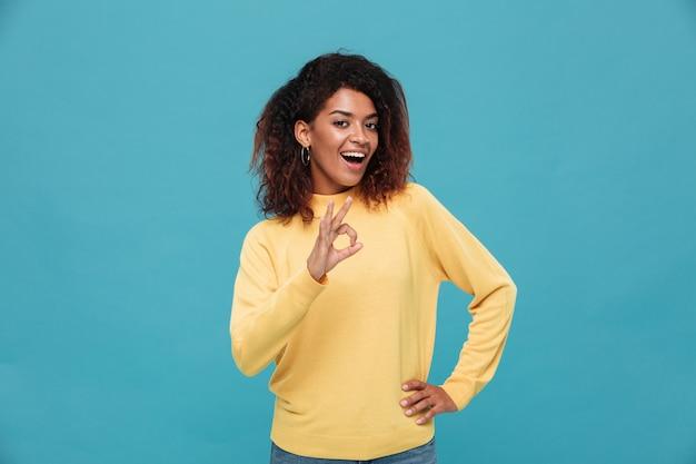 Giovane signora africana felice che mostra gesto giusto.