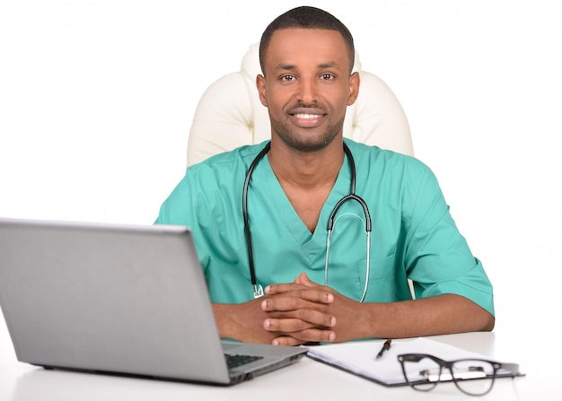 Happy young african male doctor on laptop.