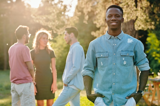 Happy young african man in denim shirt standing in park on group of his intercultural friends discusing their ideas of where to go
