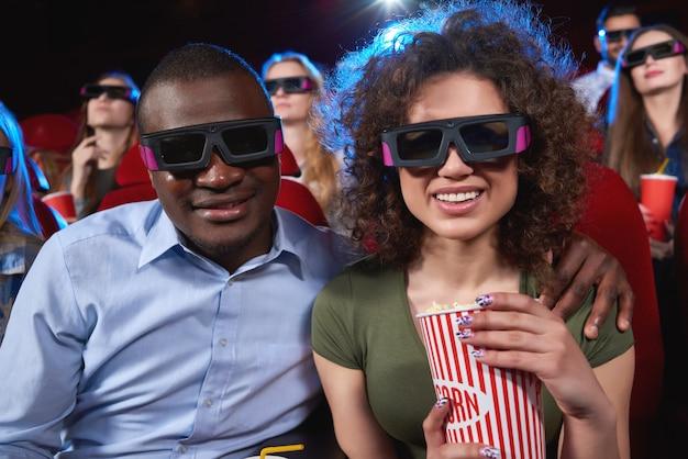 映画館で3 d映画を一緒に見て楽しんでいる間彼の美しい陽気なガールフレンドを抱きしめる幸せな若いアフリカ人は現代の人々レジャー技術デートポップコーン関係を食べています。