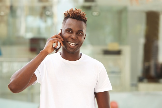 Happy young african man guy making a phone call and smiling